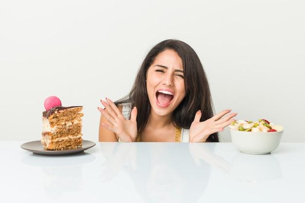 Jovem mulher hispânica, escolhendo entre bolo ou fruta comemorando uma vitória ou sucesso