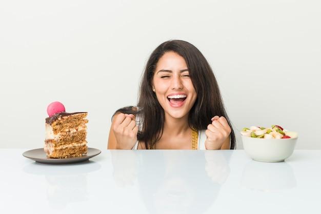 Jovem mulher hispânica, escolhendo entre bolo ou fruta torcendo despreocupado e animado.