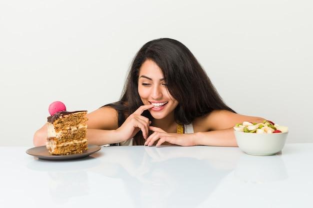 Jovem mulher hispânica, escolhendo entre bolo ou fruteira