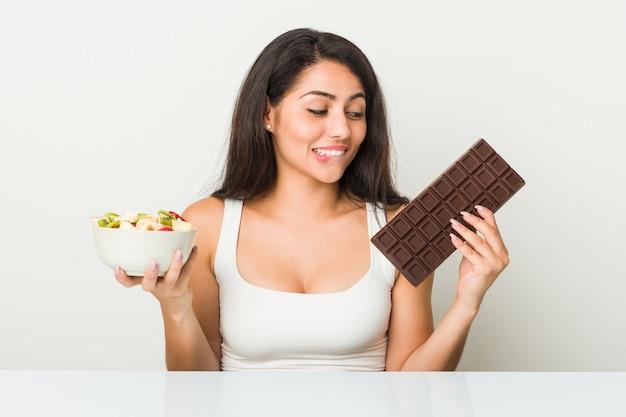 Jovem mulher hispânica, escolhendo entre tablete de maçã ou chocolate