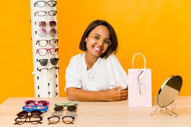 Jovem mulher hispânica experimentando óculos isolado feliz, sorridente e alegre.