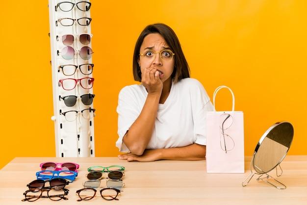 Jovem mulher hispânica experimentando óculos isolado roer as unhas, nervosa e muito ansiosa.