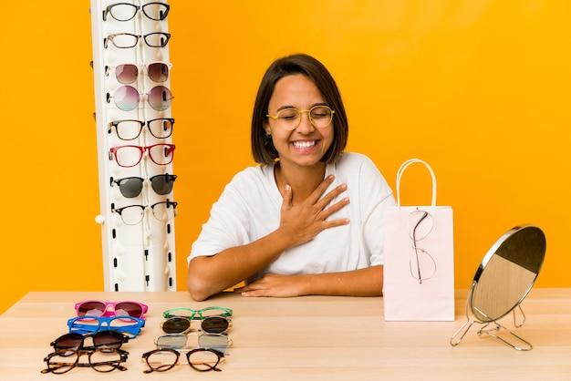 Jovem mulher hispânica experimentando óculos isolados ri alto, mantendo a mão no peito.