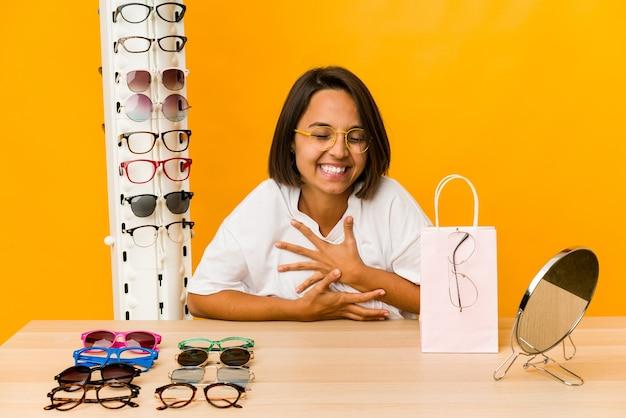 Jovem mulher hispânica experimentando óculos isolados, rindo e se divertindo.