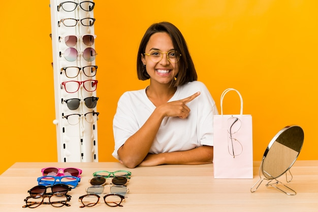 Jovem mulher hispânica experimentando óculos isolados sorrindo e apontando de lado, mostrando algo no espaço em branco.