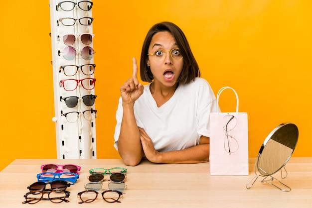 Jovem mulher hispânica experimentando óculos isolados, tendo uma ideia, o conceito de inspiração.