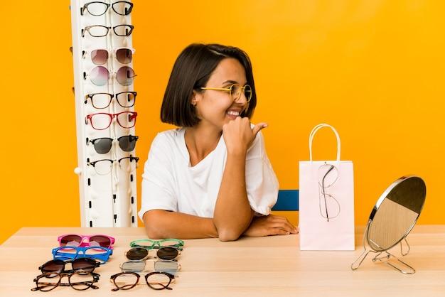Jovem mulher hispânica experimentando pontos isolados de óculos com o dedo polegar de distância, rindo e despreocupada.