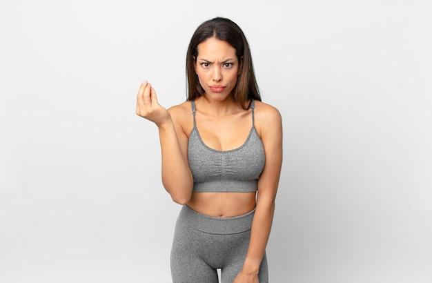 Jovem mulher hispânica fazendo capice ou gesto de dinheiro, dizendo para você pagar. conceito de fitness