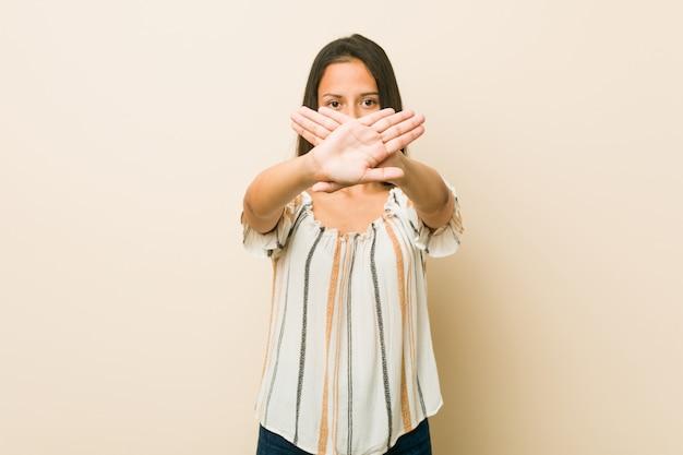 Jovem mulher hispânica, fazendo um gesto de negação