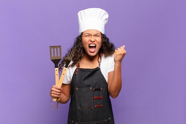 Jovem mulher hispânica gritando agressivamente com uma expressão de raiva ou com os punhos cerrados celebrando o sucesso. conceito de chef de churrasco