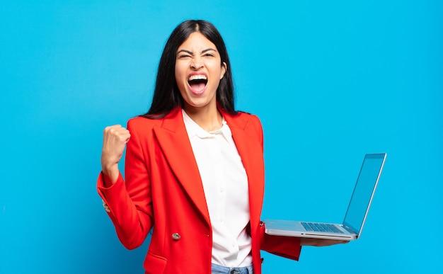 Jovem mulher hispânica gritando agressivamente com uma expressão de raiva ou com os punhos cerrados celebrando o sucesso. conceito de laptop