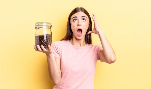 Jovem mulher hispânica gritando com as mãos no ar. conceito de grãos de café