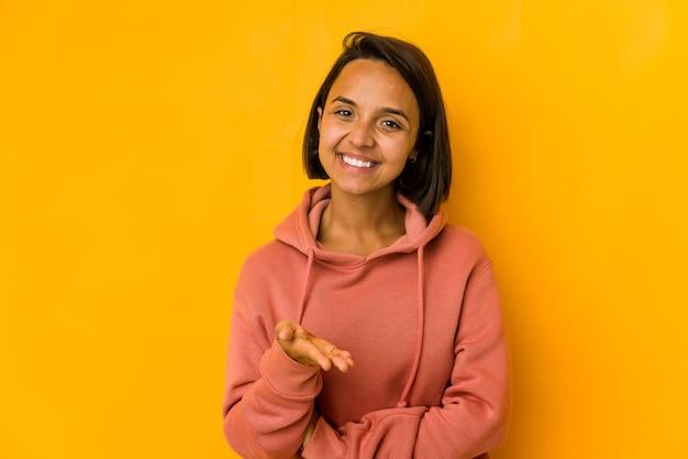 Jovem mulher hispânica isolada em amarelo, esticando a mão para a câmera em um gesto de saudação.