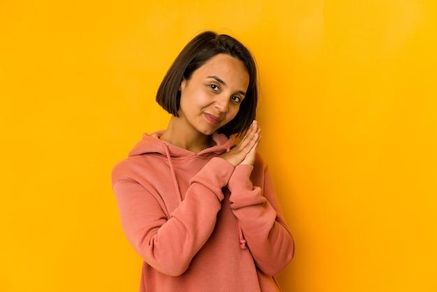 Jovem mulher hispânica isolada em amarelo, sentindo-se enérgica e confortável, esfregando as mãos com confiança.