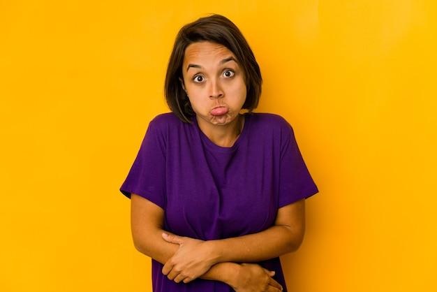 Jovem mulher hispânica isolada em ombros amarelos encolhe os ombros e olhos abertos confusos.
