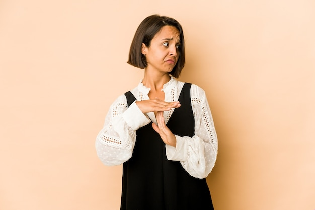 Jovem mulher hispânica isolada, mostrando um gesto de tempo limite.