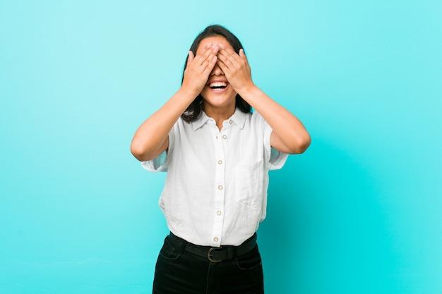 Jovem mulher hispânica legal contra uma parede azul cobre os olhos com as mãos, sorri amplamente esperando por uma surpresa.