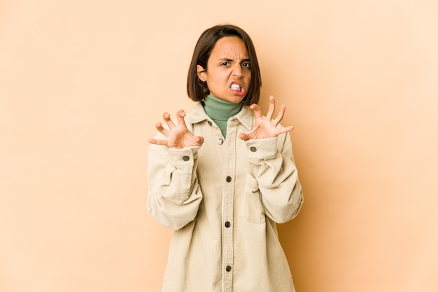 Jovem mulher hispânica mostrando garras imitando um gesto agressivo de gato.