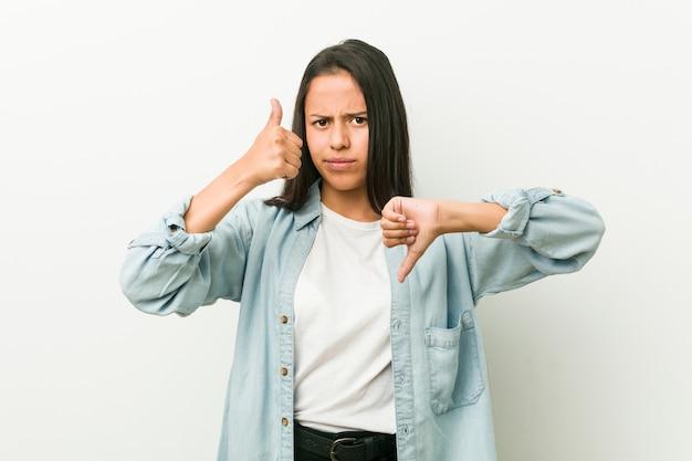 Jovem mulher hispânica, mostrando os polegares para cima e os polegares para baixo, difícil escolher