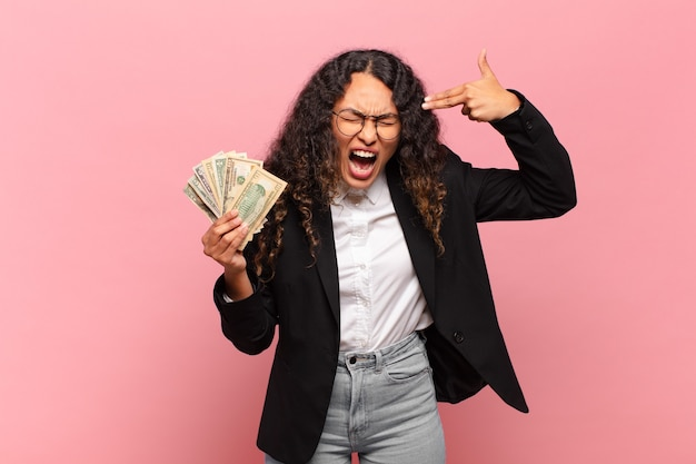 Jovem mulher hispânica olhando infeliz e estressada, gesto de suicídio fazendo sinal de arma com a mão, apontando para a cabeça. conceito de notas de dólar