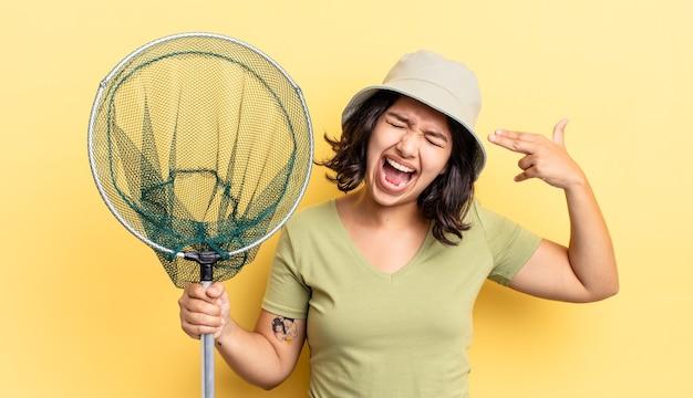 Jovem mulher hispânica olhando infeliz e estressada, gesto de suicídio fazendo sinal de arma. conceito de rede de pesca