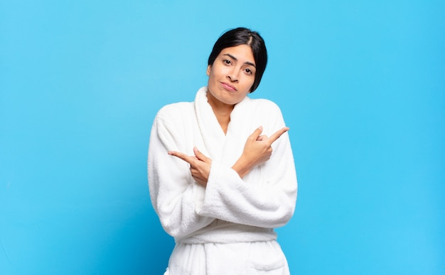 Jovem mulher hispânica olhando perplexa e confusa, insegura e apontando em direções opostas com dúvidas. conceito de roupão de banho