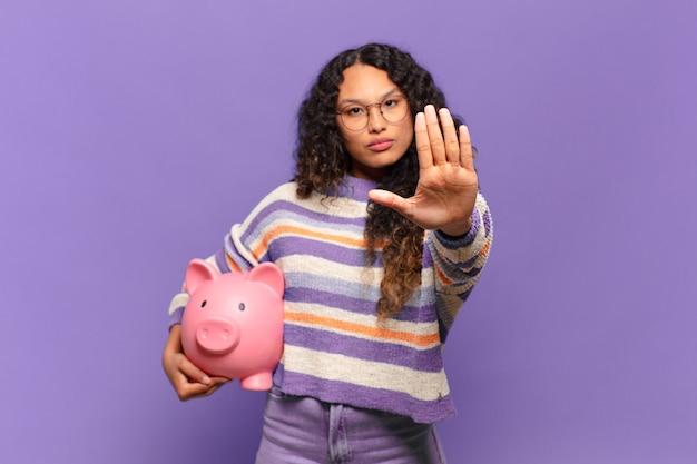 Jovem mulher hispânica olhando séria, severa, descontente e com raiva, mostrando a palma da mão aberta, fazendo gesto de parada. conceito de cofrinho