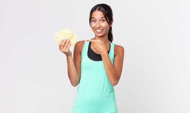 Jovem mulher hispânica parecendo animada e surpresa, apontando para o lado. conceito de dieta de fitness