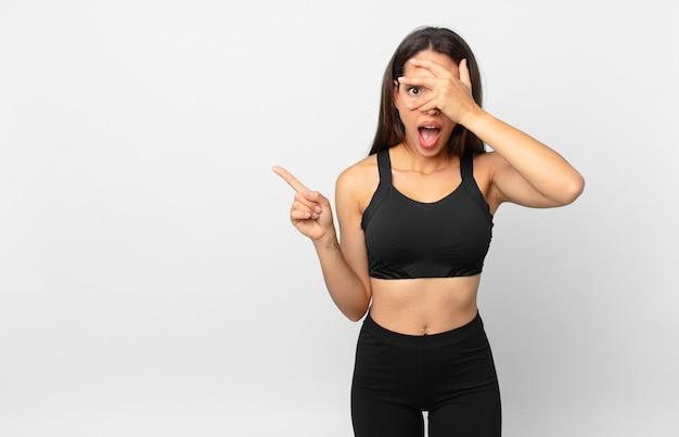 Jovem mulher hispânica parecendo chocada, assustada ou apavorada, cobrindo o rosto com a mão. conceito de fitness