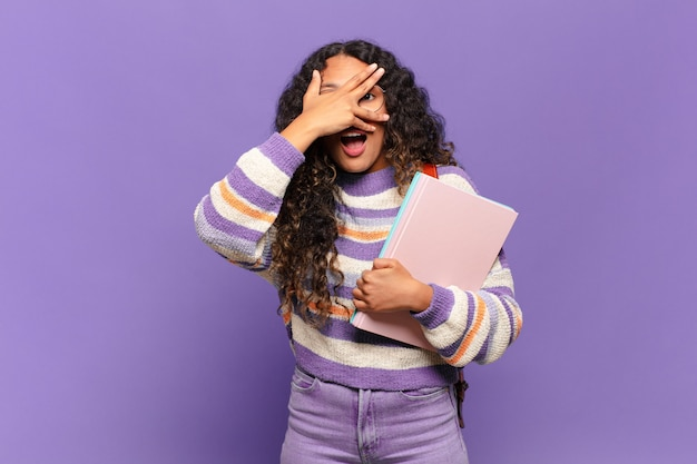 Jovem mulher hispânica parecendo chocada, assustada ou apavorada, cobrindo o rosto com a mão e espiando por entre os dedos. conceito de estudante