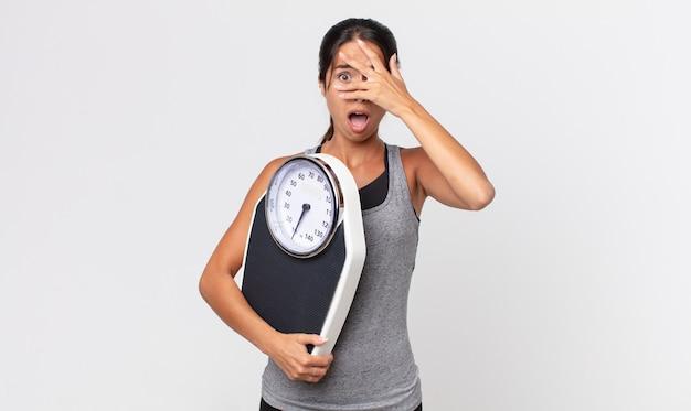 Jovem mulher hispânica parecendo chocada, assustada ou apavorada, cobrindo o rosto com a mão e segurando uma balança. conceito de dieta
