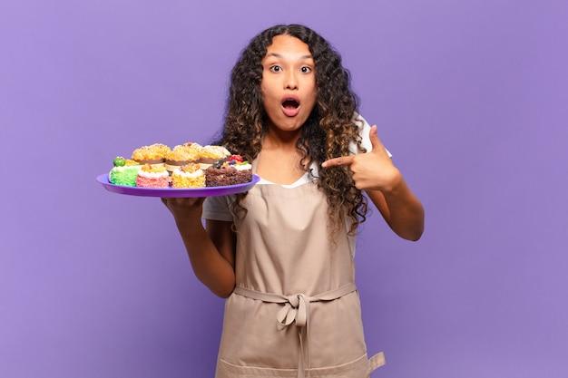 Jovem mulher hispânica parecendo chocada e surpresa com a boca aberta, apontando para si mesma. conceito de bolos de cozinha