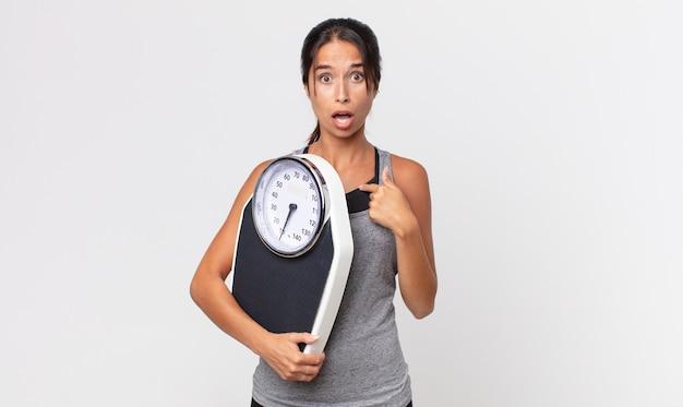 Jovem mulher hispânica parecendo chocada e surpresa com a boca aberta, apontando para si mesma e segurando uma balança. conceito de dieta