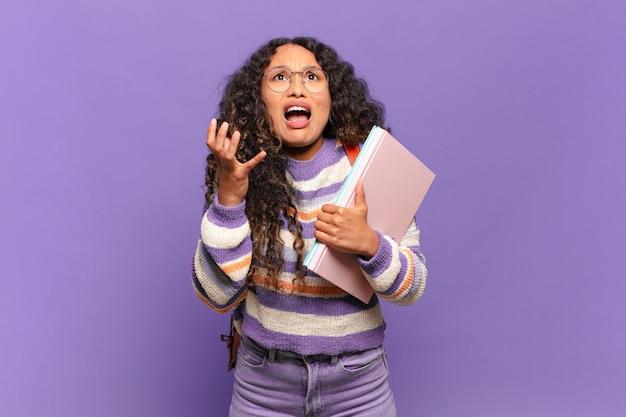 Jovem mulher hispânica parecendo desesperada e frustrada, estressada, infeliz e irritada, gritando e gritando. conceito de estudante