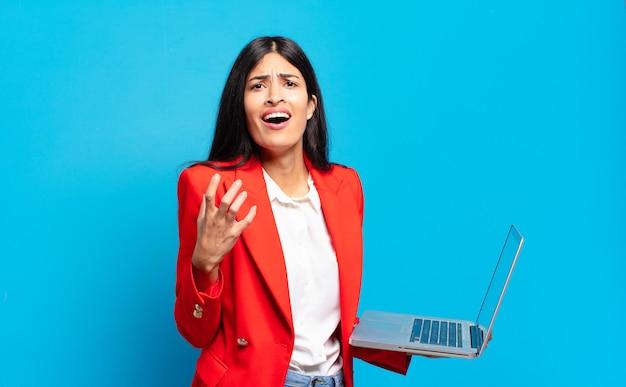 Jovem mulher hispânica parecendo desesperada e frustrada, estressada, infeliz e irritada, gritando e gritando. conceito de laptop