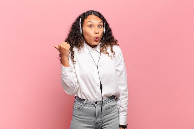 Jovem mulher hispânica parecendo espantada em descrença, apontando para o objeto ao lado e dizendo uau, inacreditável. conceito de telemarketing
