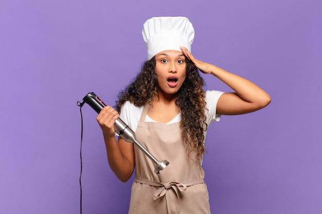 Jovem mulher hispânica parecendo feliz, atônita e surpresa, sorrindo e percebendo uma boa notícia incrível. conceito de chef