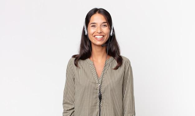 Jovem mulher hispânica parecendo feliz e agradavelmente surpresa com um fone de ouvido. conceito de telemarketing