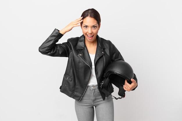 Jovem mulher hispânica parecendo feliz, espantada e surpresa. conceito de motociclista