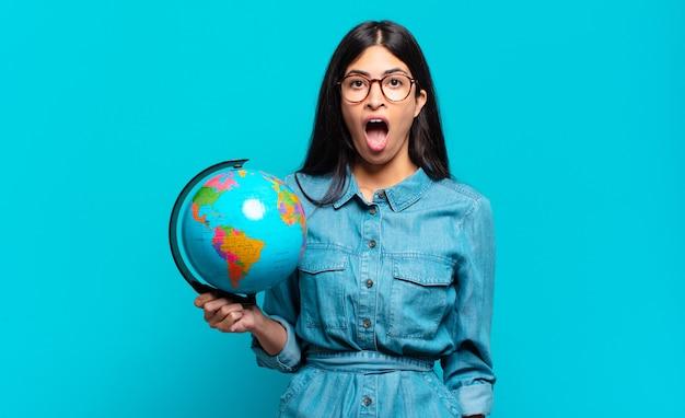 Jovem mulher hispânica parecendo muito chocada ou surpresa, olhando com a boca aberta e dizendo uau. conceito de planeta terra