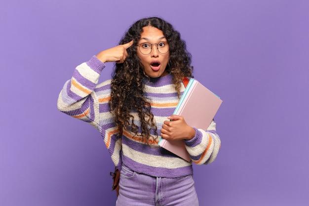 Jovem mulher hispânica parecendo surpresa, boquiaberta, chocada, percebendo um novo pensamento, ideia ou conceito. conceito de estudante