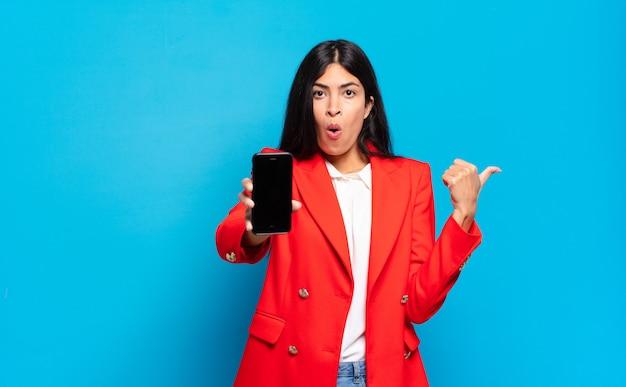Jovem mulher hispânica parecendo surpresa em descrença, apontando para um objeto ao lado e dizendo uau, inacreditável