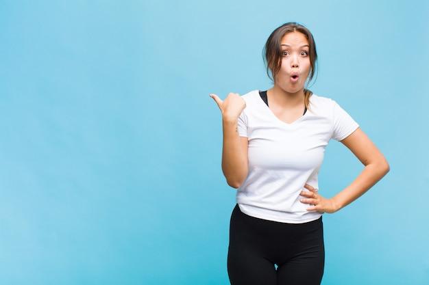 Jovem mulher hispânica parecendo surpresa em descrença, apontando para um objeto na lateral e dizendo uau, inacreditável