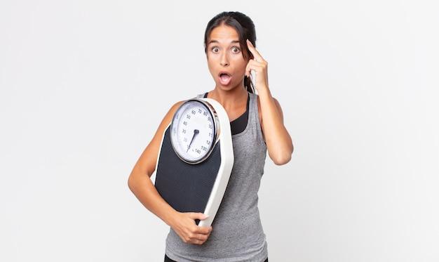 Jovem mulher hispânica parecendo surpresa, percebendo um novo pensamento, ideia ou conceito e segurando uma balança. conceito de dieta