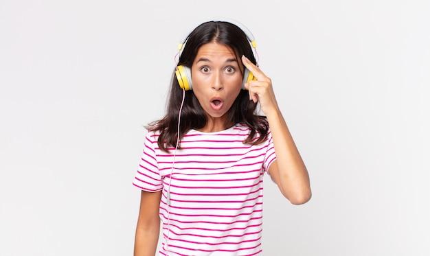 Jovem mulher hispânica parecendo surpresa, percebendo um novo pensamento, ideia ou conceito ouvindo música com fones de ouvido