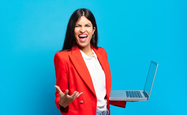 Jovem mulher hispânica parecendo zangada, irritada e frustrada gritando wtf ou o que há de errado com você. conceito de laptop