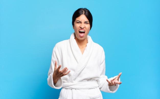 Jovem mulher hispânica parecendo zangada, irritada e frustrada gritando wtf ou o que há de errado com você. conceito de roupão de banho