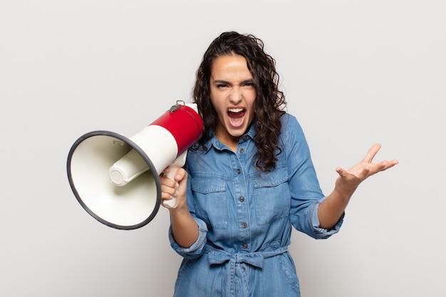 Jovem mulher hispânica parecendo zangada, irritada e frustrada gritando wtf ou o que há de errado com você