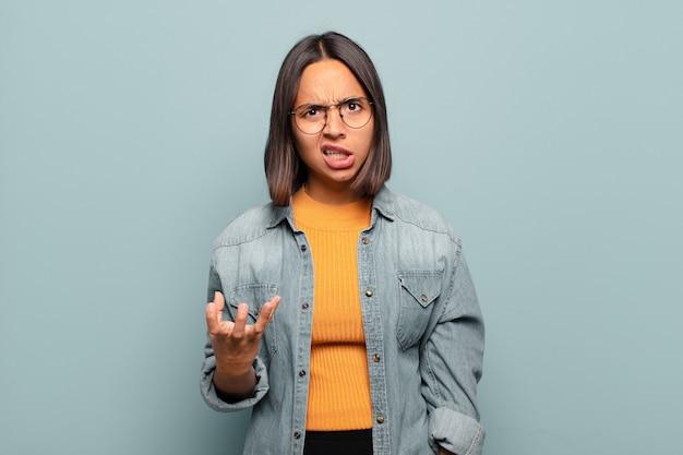 Jovem mulher hispânica parecendo zangada, irritada e frustrada gritando wtf