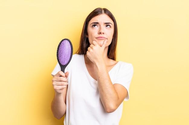 Jovem mulher hispânica pensando, sentindo-se duvidosa e confusa. conceito de escova de cabelo